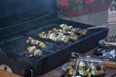 Os espetos com fatias de batatas, abobrinha, bacon, cogumelos, cebola, couve-rábano grelharam sobre os carvões vegetais na grade  fotografia de stock royalty free