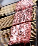 Os espetos da carne roasted em carvões de incandescência para a venda imagem de stock