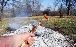 Os espetos da salsicha s?o aquecidos grelhando em um fogo lento especial por muito tempo a comer como um caf? da manh? da fam?lia foto de stock