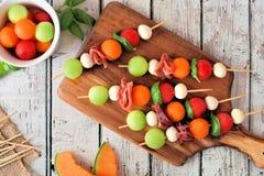 Os espetos do fruto do verão em um serviço de madeira embarcam Imagem de Stock
