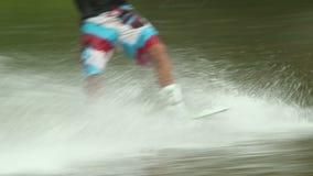 Os esportes de água da ação, pés masculinos do wakeboarder montam na superfície da água filme
