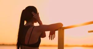 Os esportes e a sa?de das mulheres do tema Mulher caucasiano bonita com o cabelo longo encaracolado que levanta na terra de espor video estoque