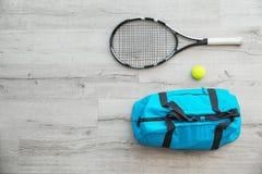 Os esportes ensacam, raquete e bola no floo de madeira imagem de stock royalty free