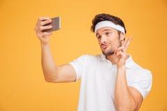 Os esportes novos de sorriso equipam a tomada do selfie e mostrar o sinal de v Foto de Stock