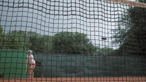 Os esportes que ganham, menina do jogador de tênis profissional batem a raquete na bola e as corridas até a rede com mãos acima e video estoque