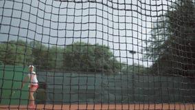 Os esportes triunfam, a menina adolescente do jogador de tênis bem sucedido bate a raquete na bola e as corridas até a rede com m vídeos de arquivo