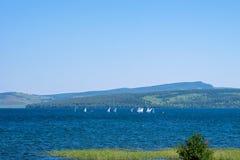 Os esportes yachts no lago, com madeira e bastão, no primeiro plano foto de stock