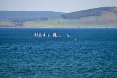 Os esportes yachts no lago, contra o contexto das montanhas fotografia de stock royalty free