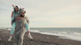 Os esposos felizes no kigurumi trajam o corredor em uma praia de pedra perto do mar vídeos de arquivo