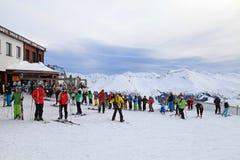 Os esquiadores apreciam esquiar na inclinação nos cumes austríacos Fotos de Stock Royalty Free