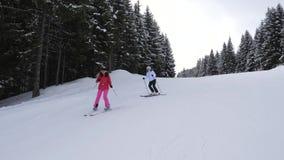 Os esquiadores das mulheres montam um após o outro em Ski In The Mountains On Forest Track video estoque