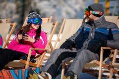 Os esquiadores dos pares relaxam nas cadeiras na parte superior da montanha Imagens de Stock