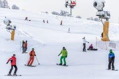 Os esquiadores e os snowboarders que montam em um esqui nevado inclinam-se Foto de Stock Royalty Free