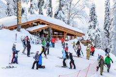 Os esquiadores e os snowboarders que montam em um esqui nevado inclinam-se Fotos de Stock