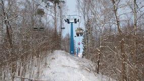 Os esquiadores e os snouborders em um elevador de esqui pov na floresta do inverno o teleférico levantam os povos até a inclinaçã video estoque