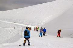 Os esquiadores e os snowboarders que montam em um esqui inclinam-se Foto de Stock
