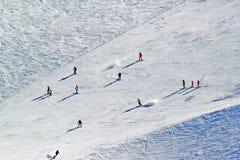 Os esquiadores e os snowboarders que montam em um esqui inclinam-se Fotos de Stock Royalty Free