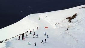 Os esquiadores e os snowboarders que montam em um esqui inclinam-se Imagem de Stock Royalty Free