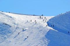 Os esquiadores e os snowboarders que montam em um esqui inclinam-se Fotografia de Stock Royalty Free