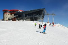 Os esquiadores estão na inclinação perto da estação do cabo aéreo em Chopok em Jasna imagem de stock royalty free
