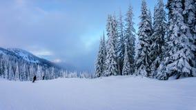 Os esquiadores que vão para baixo como a névoa estão entrando Fotografia de Stock Royalty Free
