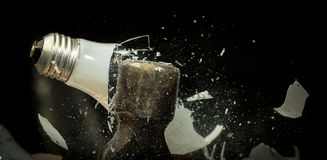 Os estilhaços de vidro despedaçados voam de uma ampola incandescente Fotografia de Stock