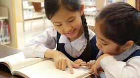 Os estudantes asiáticos pequenos com o livro de leitura uniforme na biblioteca junto, inclinam acima da câmera video estoque