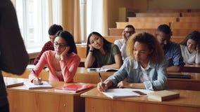 Os estudantes cansados e furados estão escutando o professor e estão fazendo anotações nos cadernos que sentam-se em mesas na uni video estoque