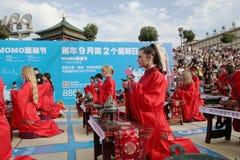 Os estudantes chineses e estrangeiros com uma bênção do hanfu recolheram na torre de pulso de disparo na cerimônia Imagens de Stock