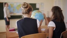 Os estudantes da High School estudam o globo durante a lição da geografia vídeos de arquivo