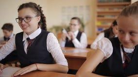 Os estudantes da High School executam o teste O estudante impertinente confunde crianças no avião de papel da classe e dos lances video estoque
