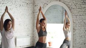 Os estudantes da ioga estão fazendo a pose da árvore do equilíbrio ao exercitar no estúdio moderno do bem-estar Instuctor que est vídeos de arquivo