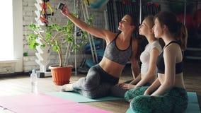Os estudantes da ioga estão tomando o selfie com smartphone ao sentar-se junto na esteira brilhante no estúdio da ioga As mulhere filme