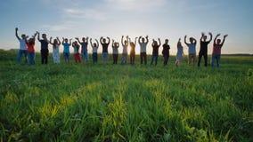 Os estudantes dizem adeus à escola Alunos que acenam suas mãos contra o contexto do sol de ajuste vídeos de arquivo