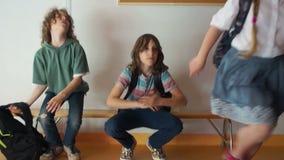 Os estudantes durante uma ruptura da escola estão sentando-se em um banco no corredor De repente, o sino soa, as crianças estão e video estoque