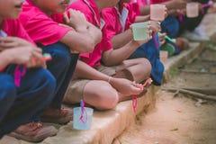 Os estudantes elementares escovam seus dentes após o almoço imagem de stock