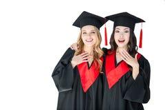 Os estudantes entusiasmado atrativos na graduação tampam o aperto isolados Imagem de Stock Royalty Free