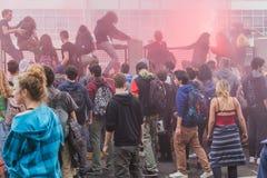 Os estudantes escalam sobre a cerca da construção da agência da educação em Milão, Itália Imagens de Stock