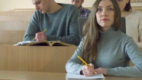 Os estudantes escrevem em seus cadernos vídeos de arquivo