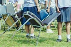 Os estudantes estão ajudando a levantar a cadeira ao meio do campo imagem de stock royalty free
