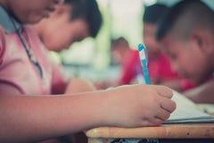 Os estudantes estão estudando na sala de aula da escola primária imagens de stock royalty free