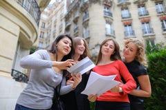Os estudantes estrangeiros que aprendem o inglês com papéis aproximam bu da universidade imagens de stock royalty free