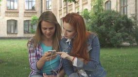Os estudantes fêmeas escutam a música no smartphone no terreno vídeos de arquivo