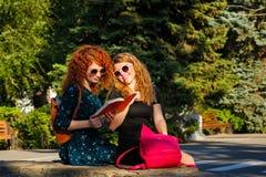 Os estudantes fêmeas leram um livro no parque Imagem de Stock