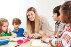 Os estudantes fazem trabalhos de casa com um professor imagem de stock