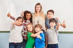 Os estudantes felizes mantêm seus polegares acima fotografia de stock