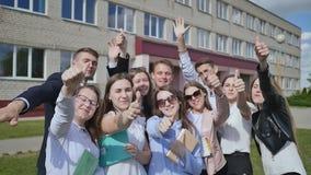 Os estudantes felizes no fundo de sua escola levantam suas mãos com um dedo acima Demonstre o sucesso e o bom humor filme