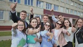 Os estudantes felizes no fundo de sua escola levantam suas mãos com um dedo acima Demonstre o sucesso e o bom humor video estoque