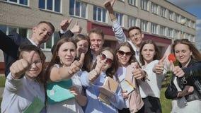 Os estudantes felizes no fundo de sua escola levantam suas mãos com um dedo acima Demonstre o sucesso e o bom humor vídeos de arquivo
