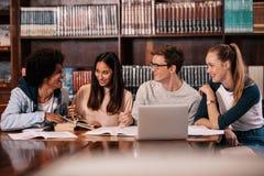 Os estudantes felizes que trabalham na faculdade projetam-se na biblioteca imagens de stock